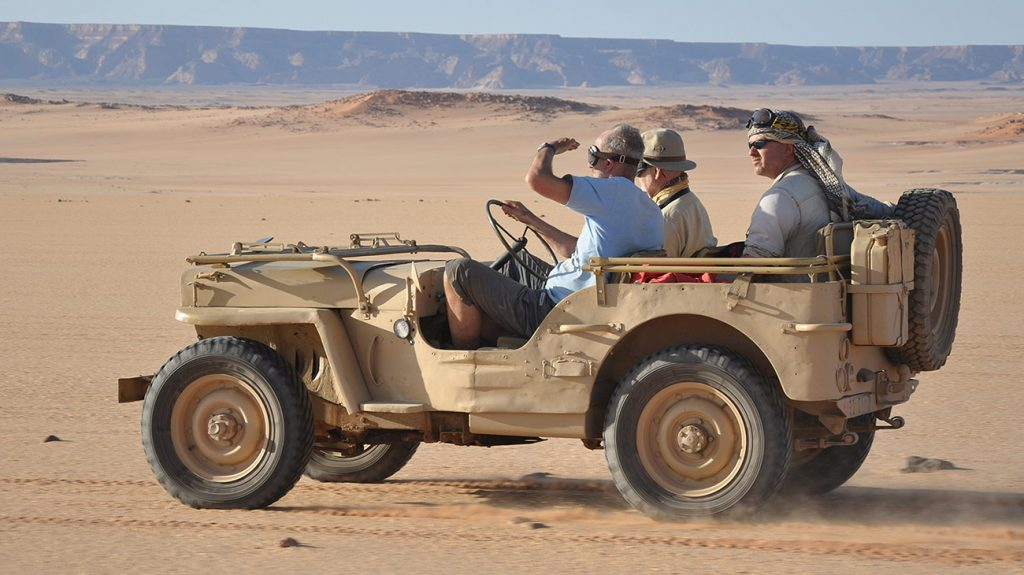 Toby Savage in a vintage jeep in the desert with friends