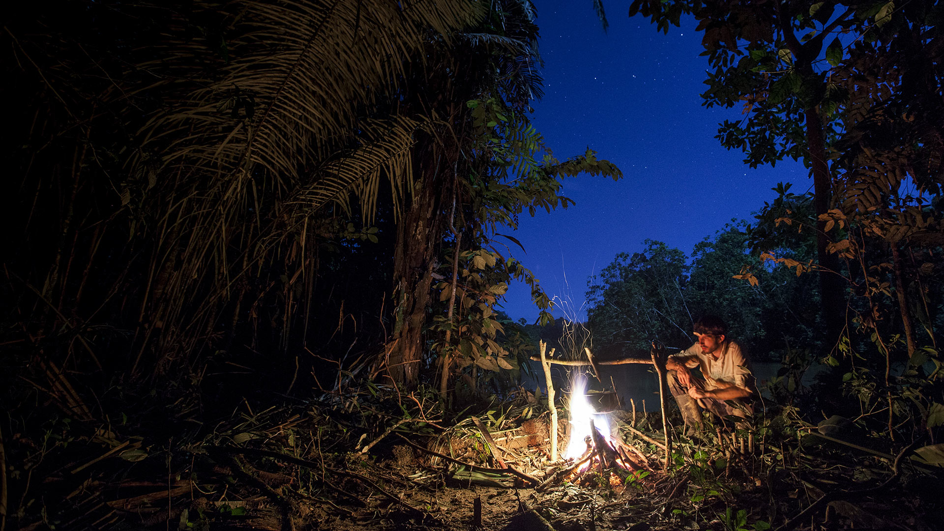 Still from Dugout with man sitting around a campfire in a jungle